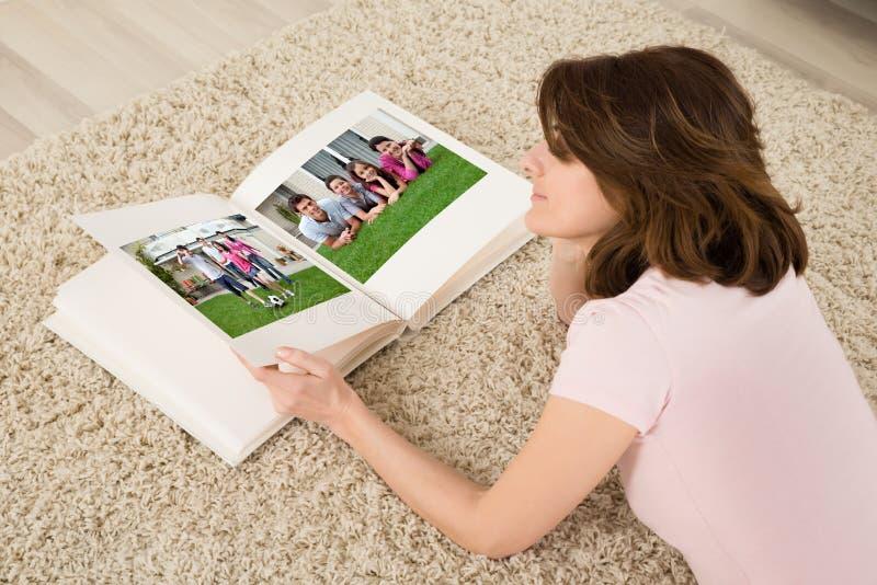 Frau, die Familien-Foto-Album betrachtet stockfotografie