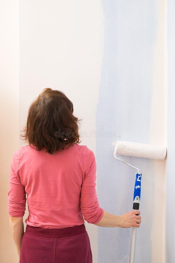 Frau, die Farbe auf Wand anwendet lizenzfreies stockbild