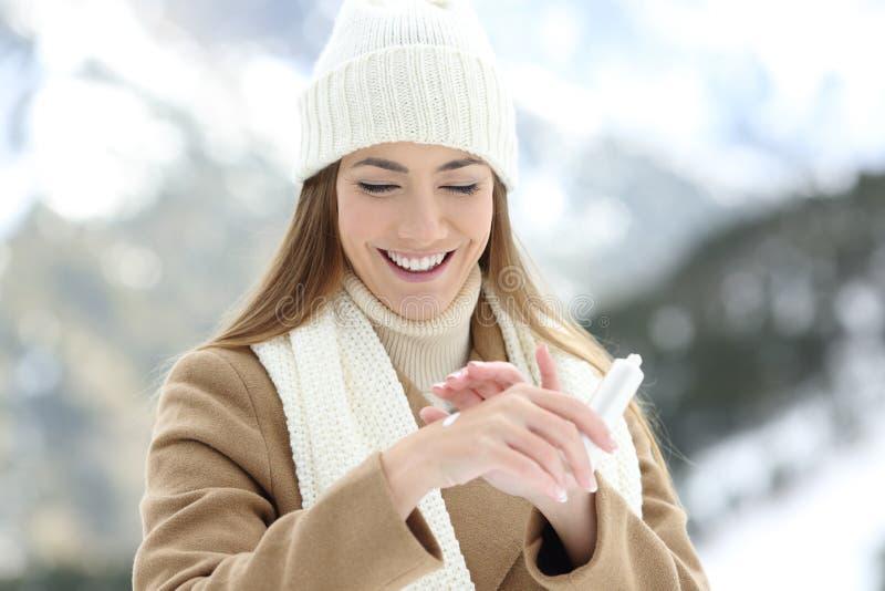 Frau, die Feuchtigkeitscremecreme auf Hydrathände zutrifft lizenzfreie stockbilder