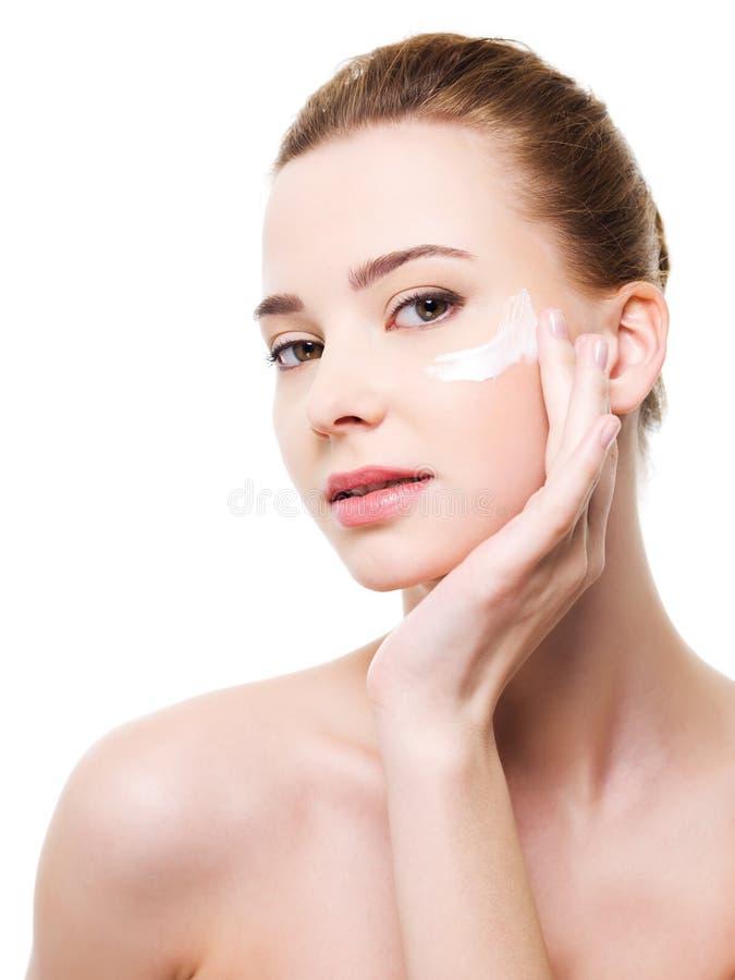Frau, die Feuchtigkeitscremekosmetik unter Augen aufträgt lizenzfreies stockbild