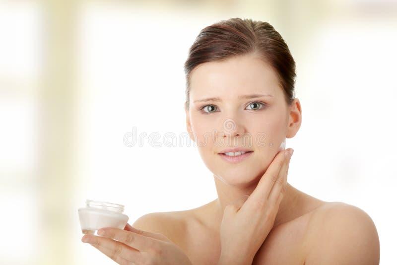 Frau, die Feuchtigkeitscremesahne auf Gesicht aufträgt stockfotos