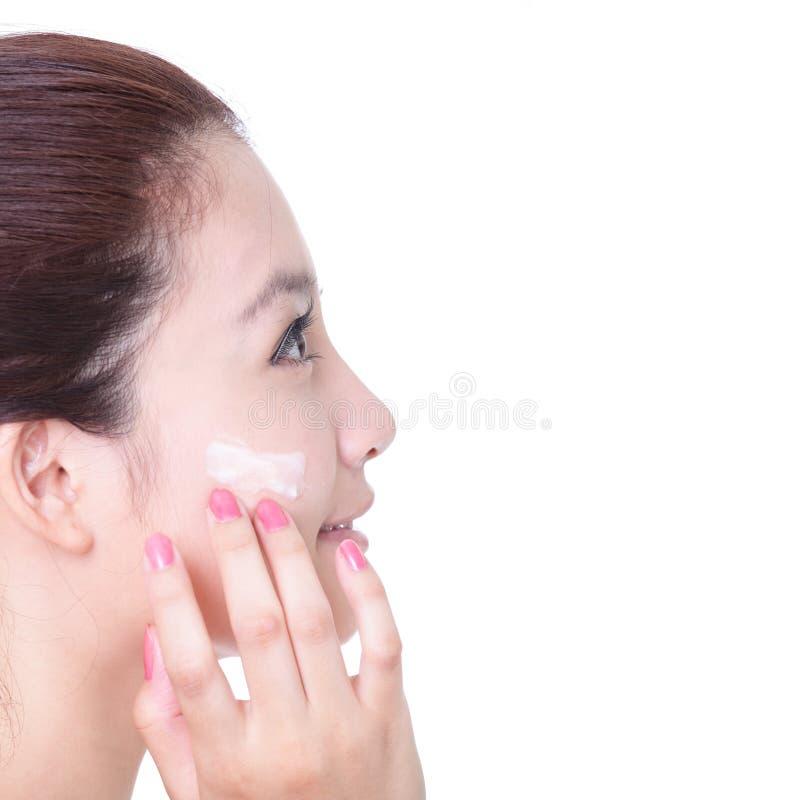 Frau, die Feuchtigkeitscremesahne im Profil aufträgt lizenzfreie stockfotos