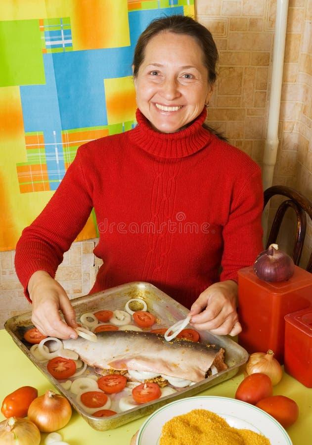 Frau, die Fische kocht stockfoto