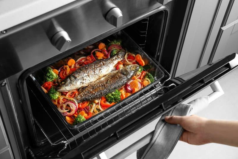 Frau, die Fische mit Gemüse kocht lizenzfreie stockfotos