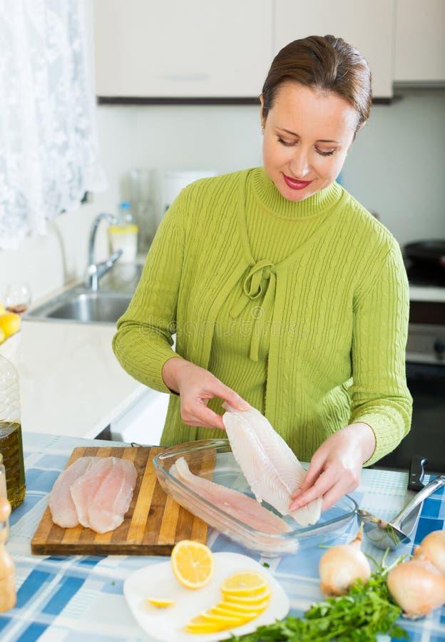 Frau, die Fische vorbereitet stockbild