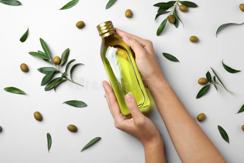 Frau, die Flasche Olivenöl auf hellem Hintergrund hält lizenzfreie stockfotos