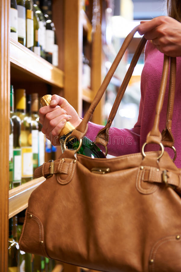 Frau, die Flasche Wein vom Shop stiehlt stockbild