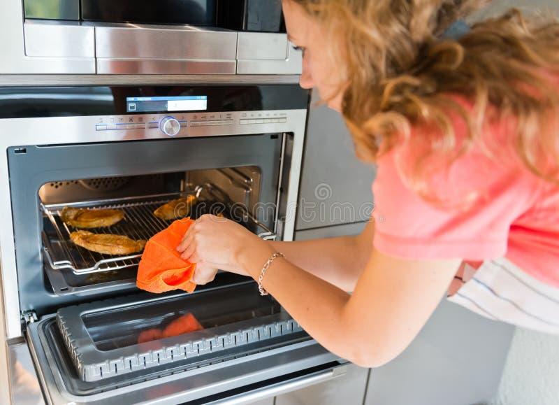 Frau, die Fleisch in Ofen setzt lizenzfreie stockbilder