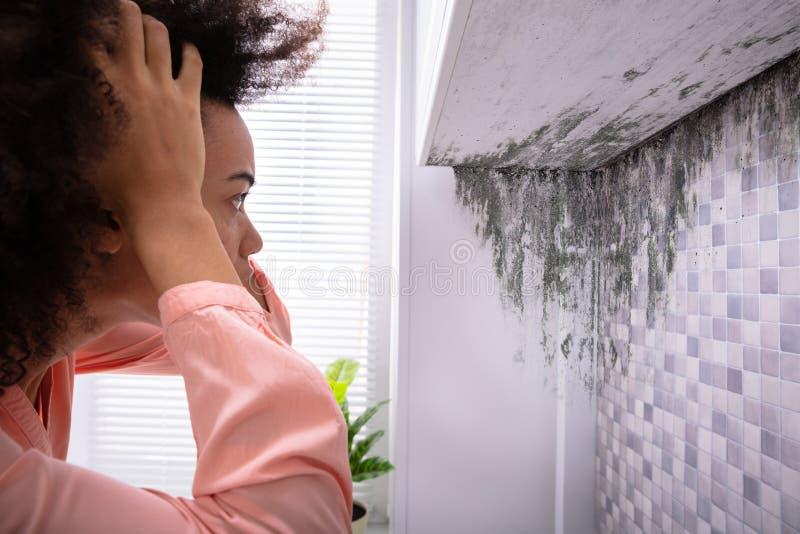 Frau, die Form auf Wand betrachtet stockbild