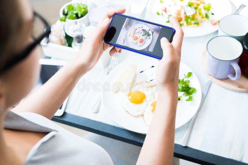 Frau, die Foto der Nahrung im Café macht stockfotos