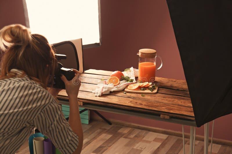 Frau, die Foto von Orangen und von Krug mit Saft macht lizenzfreie stockbilder