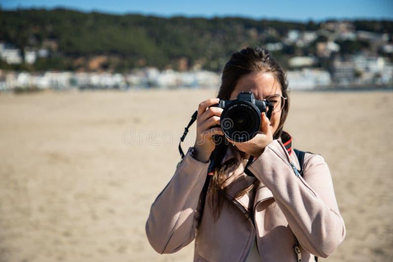 Frau, die Foto Vorderansicht mit DSLR-Kamera nimmt stockfotos