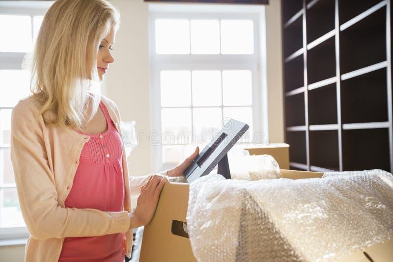 Frau, die Fotorahmen beim Auspacken von beweglichen Kästen am neuen Haus betrachtet lizenzfreie stockfotos