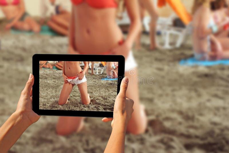 Frau, die Fotos auf eine Tablette Mädchen auf einem Strand macht stockfotografie