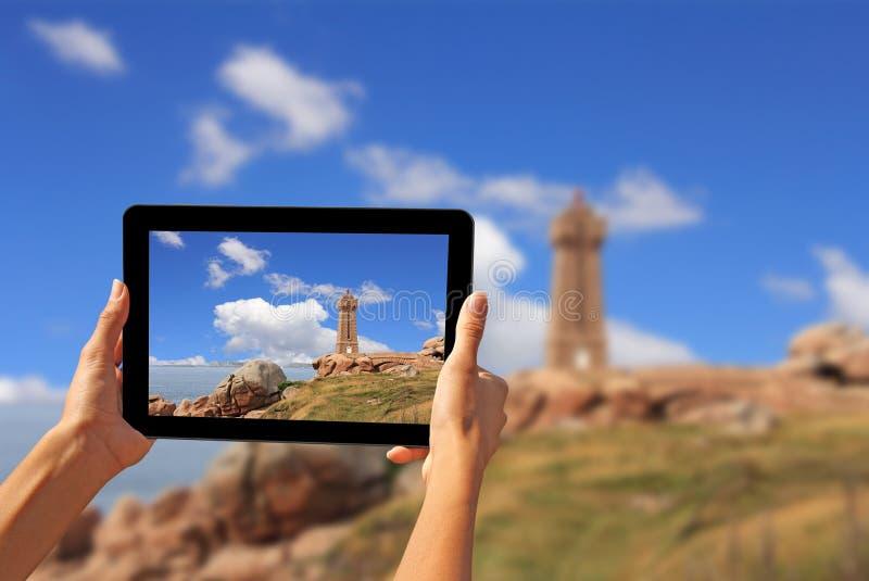 Frau, die Fotos auf einem Tablettenleuchtturm macht lizenzfreies stockfoto