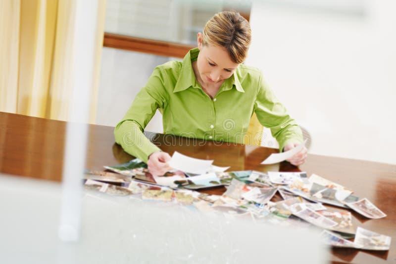 Frau, die Fotos betrachtet lizenzfreie stockfotos