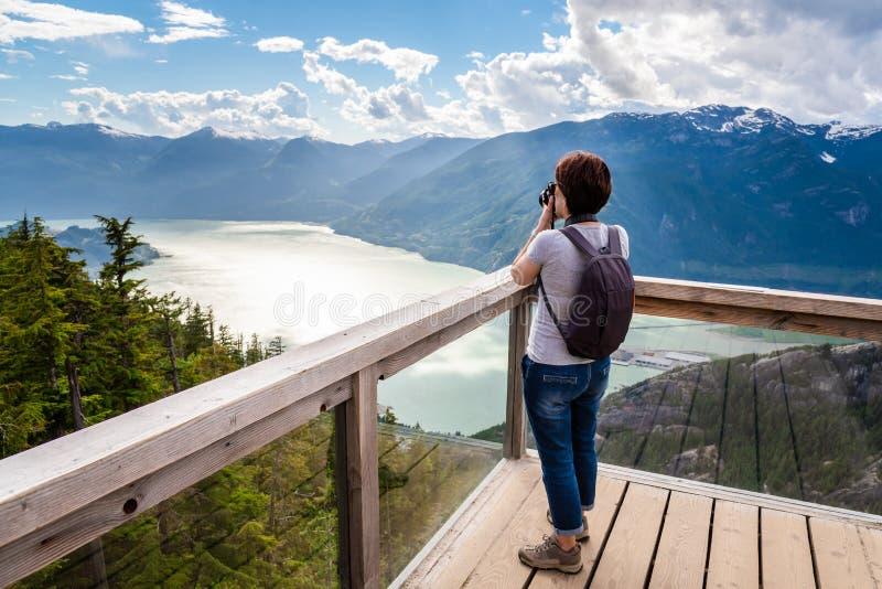 Frau, die Fotos mit ihrer DSRL-Kamera von der Spitze eines Berges macht stockfoto