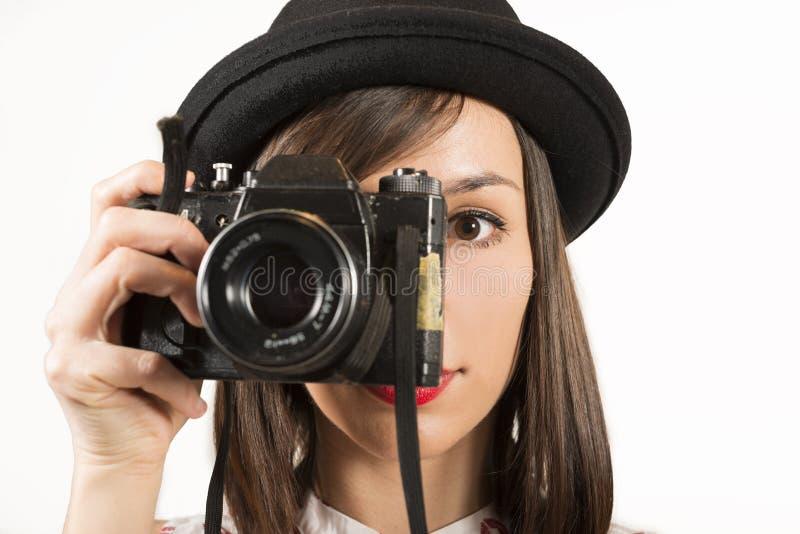 Frau, die Fotos mit Weinlesefilmkamera macht stockbild