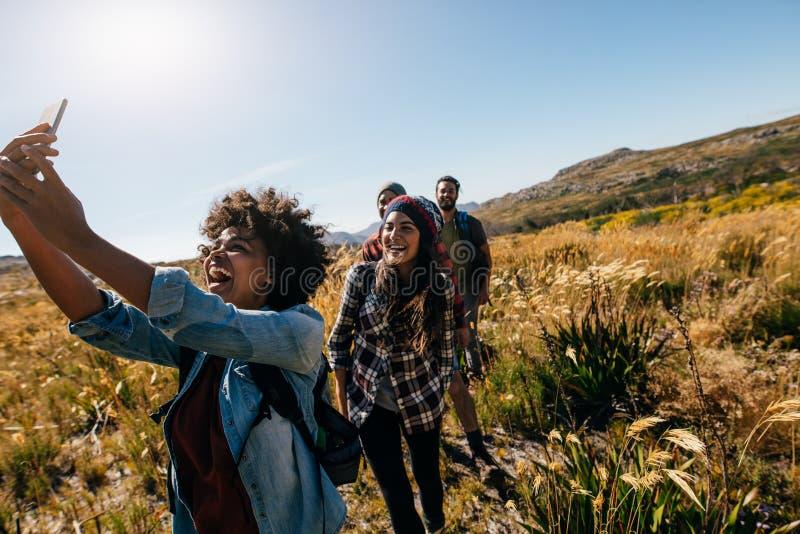 Frau, die Fotos von Freunden beim Wandern macht lizenzfreie stockfotos