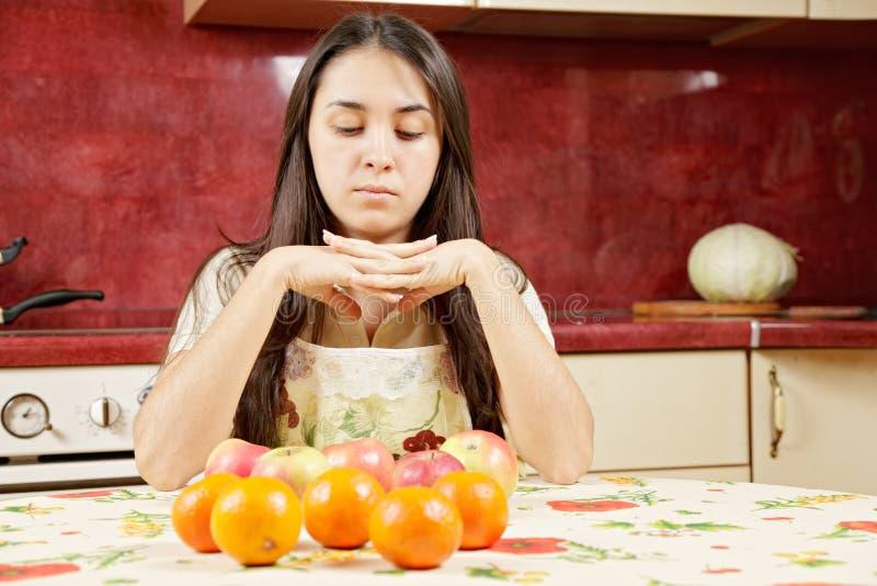 Frau, die Früchte betrachtet stockbild