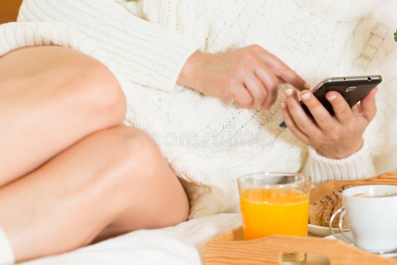 Frau, die Frühstück im Bett isst Glückliche Frau, die morgens Corn-Flakesgetreide im Bett genießt lizenzfreies stockfoto