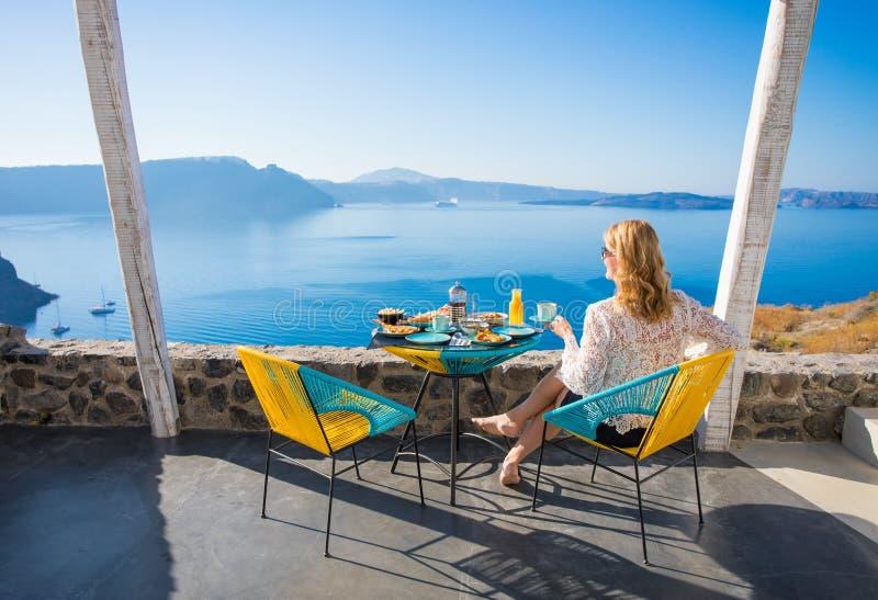 Frau, die Frühstück mit schöner Ansicht von der Terrasse genießt stockfotografie
