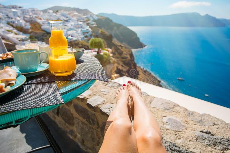 Frau, die Frühstück in schönem Santorini genießt lizenzfreie stockfotos