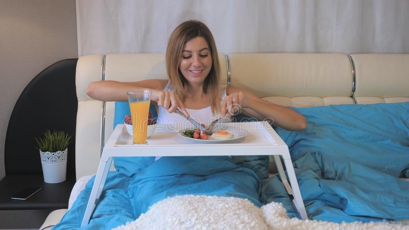 Frau, die Frühstücks-Würste mit Fried Eggs On The Table, liegend im Bett isst stockfotos