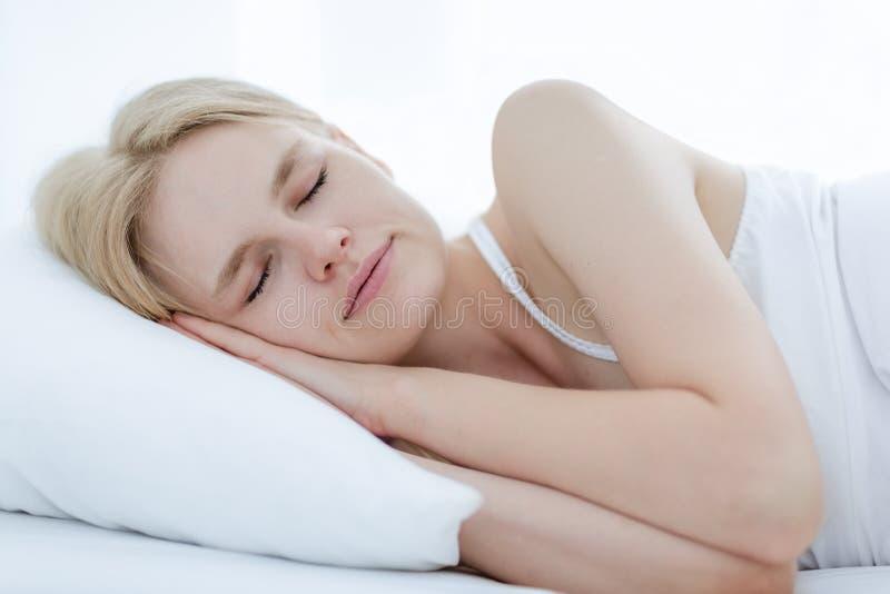Frau, die friedlich auf einem weichen weißen Bett schläft lizenzfreies stockbild