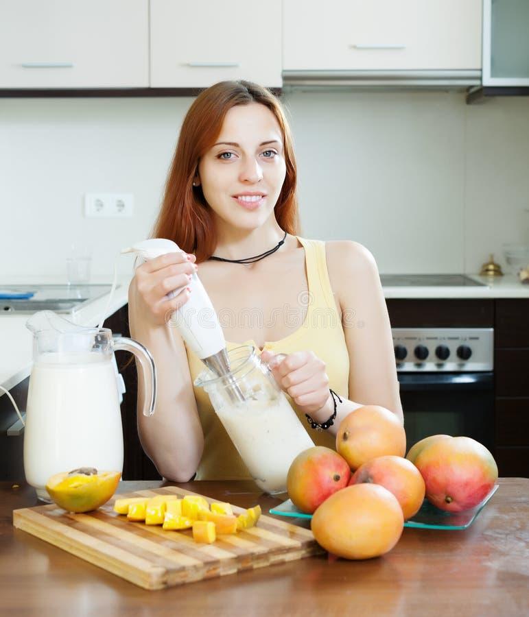 Frau, die frische Milchgetränke macht stockfotografie