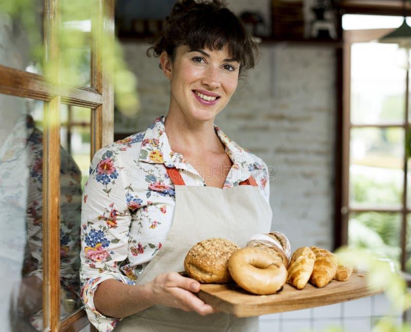 Frau, die frisches gebackenes Brot auf hölzernem Behälter hält stockfoto