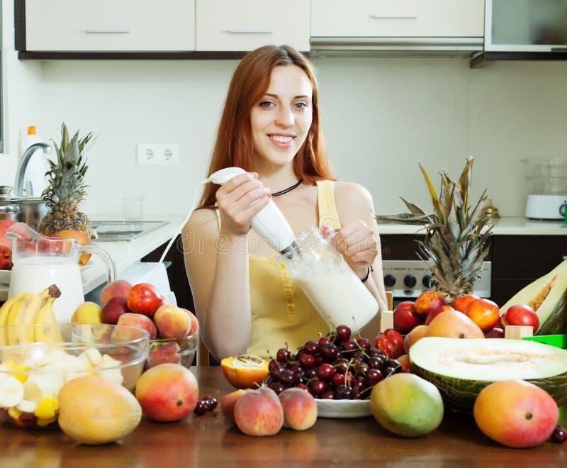 Frau, die frisches Milchcocktail macht lizenzfreies stockbild