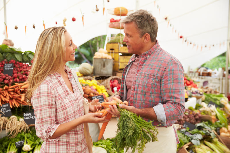 Frau, die Frischgemüse am Landwirt-Markt-Stall kauft lizenzfreies stockfoto