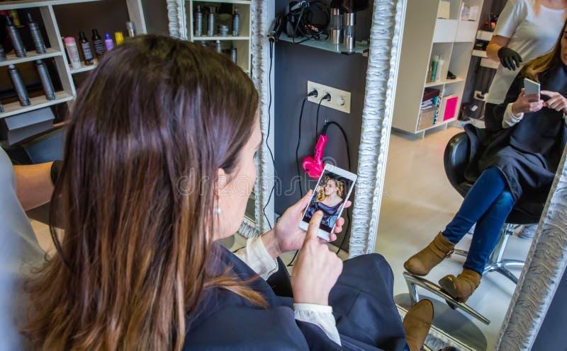 Frau, die Frisurfoto im Smartphone zu zeigt lizenzfreie stockbilder
