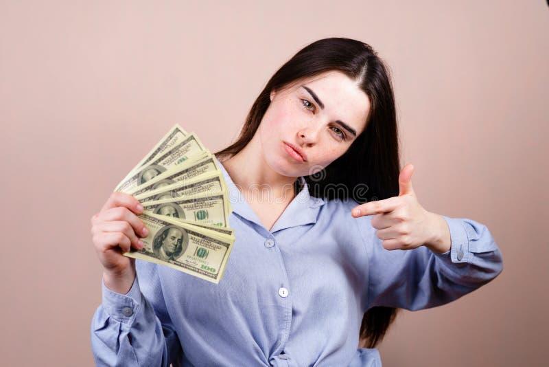 Frau, die froh in ihrem Handlos Dollar h?lt lizenzfreies stockfoto