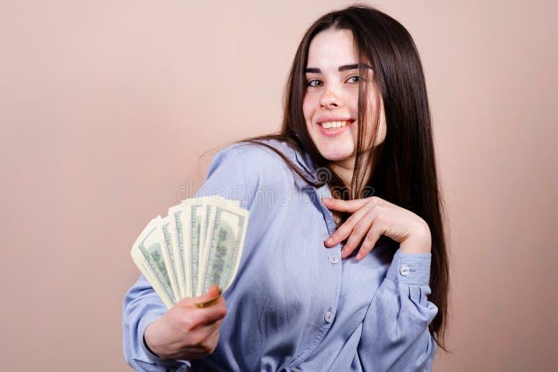 Frau, die froh in ihrem Handlos Dollar h?lt stockbilder