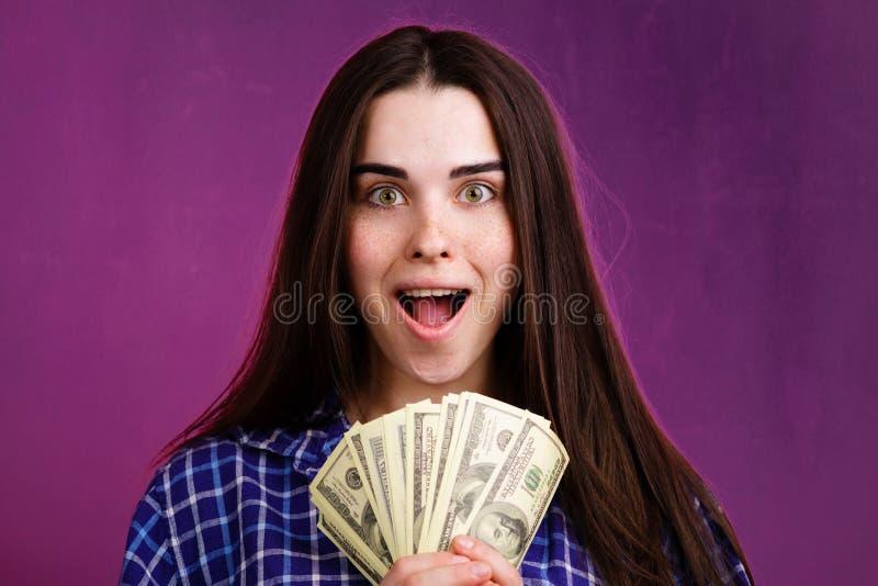 Frau, die froh in ihrem Handlos Dollar h?lt stockfotografie