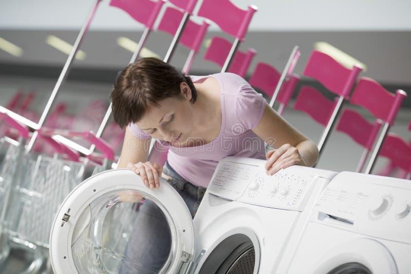 Frau, die Front Loader Of Washing Machine überprüft lizenzfreies stockfoto