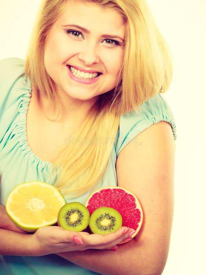 Frau, die Fruchtkiwi h?lt Orange, Zitrone und Pampelmuse lizenzfreies stockbild