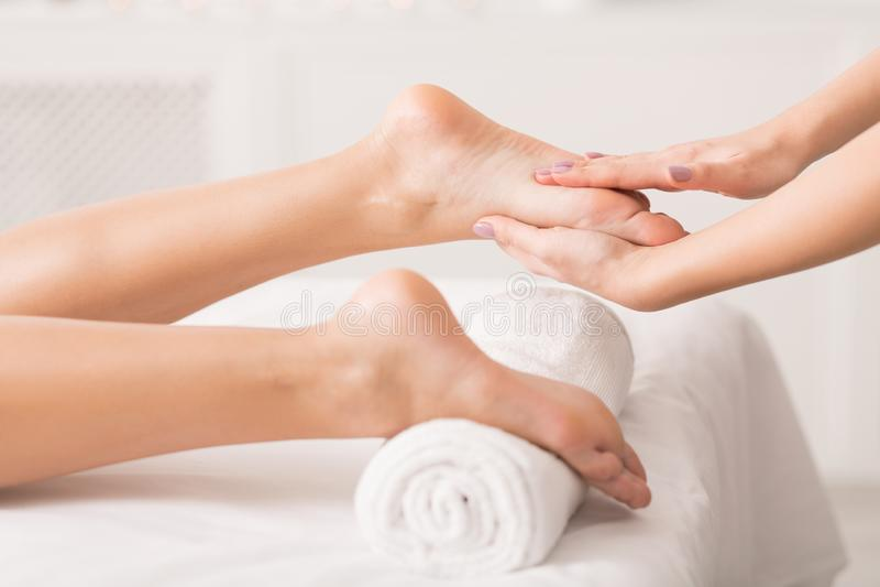 Frau, die Fußmassage am Gesundheitsbadekurort empfängt stockfotos