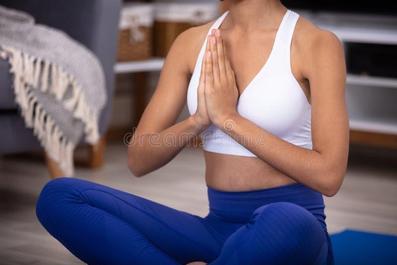 Frau, die in Gebets-Position sitzt stockfotografie