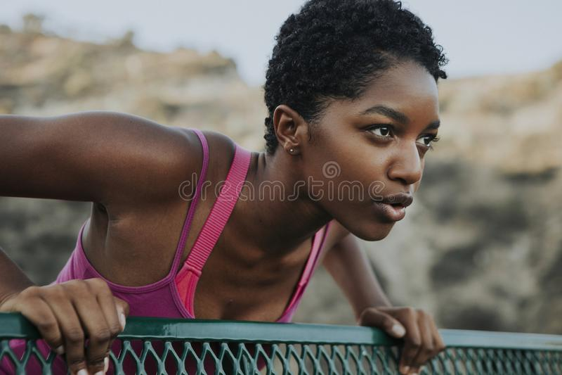 Frau, die gegen eine Parkbank ausdehnt stockfoto