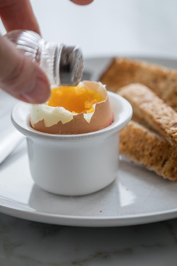 Frau, die gekochtes braunes Ei mit Eierbecher, Salzschüttel-apparat und ganzem Korntoasttoastbrot zum Frühstück salzt und isst stockbilder