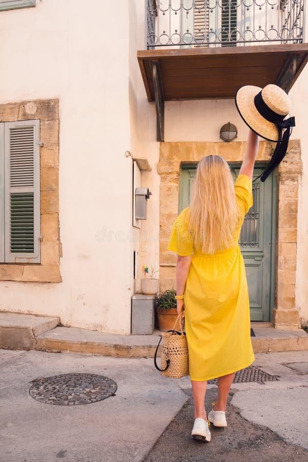 Frau, die in gelbes Kleid an alter Stadt Paphos geht stockfoto