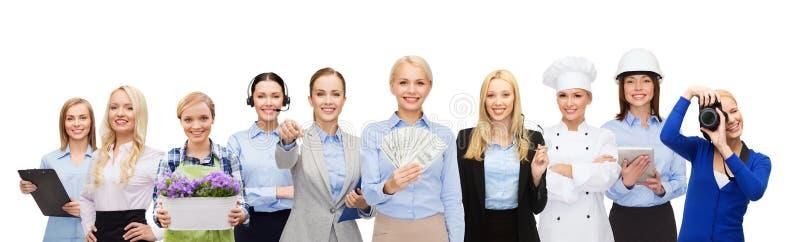 Frau, die Geld über Berufsarbeitskräften hält stockfoto