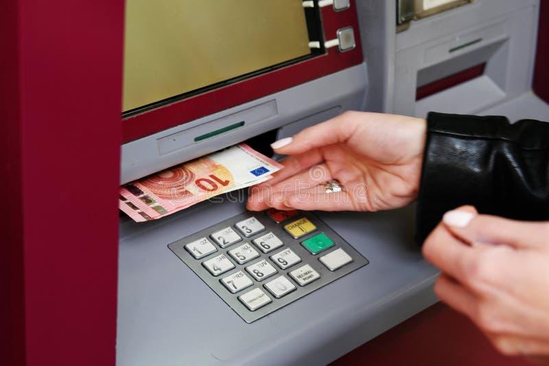 Frau, die Geld vom ATM zurücknimmt stockbilder