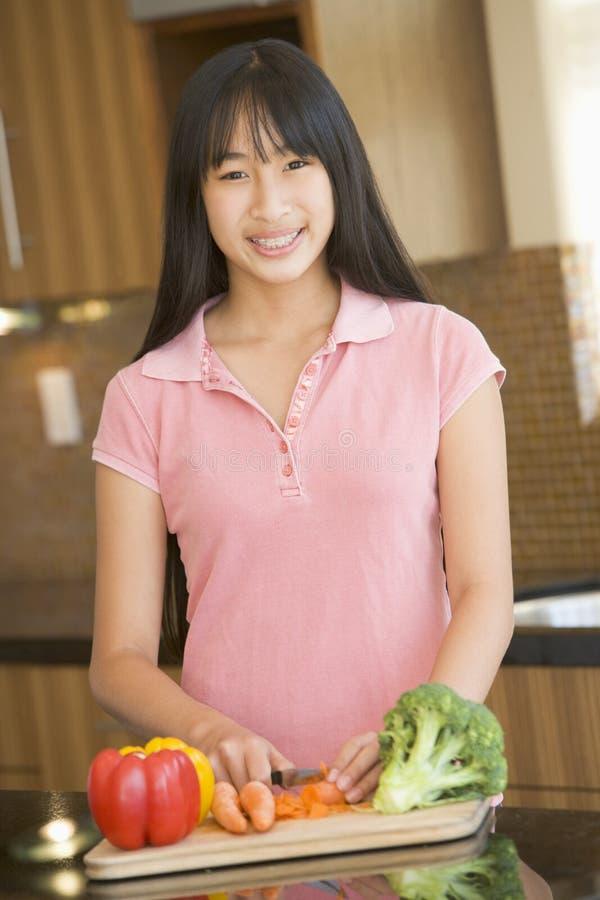 Frau, die Gemüse hackt stockbild