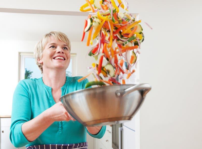 Frau, die Gemüse im Wok wirft, während kochend stockfoto