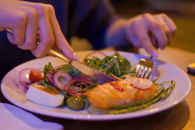 Frau, die Gemüsesalat mit Lachsen an einem Restaurant isst stockfotos