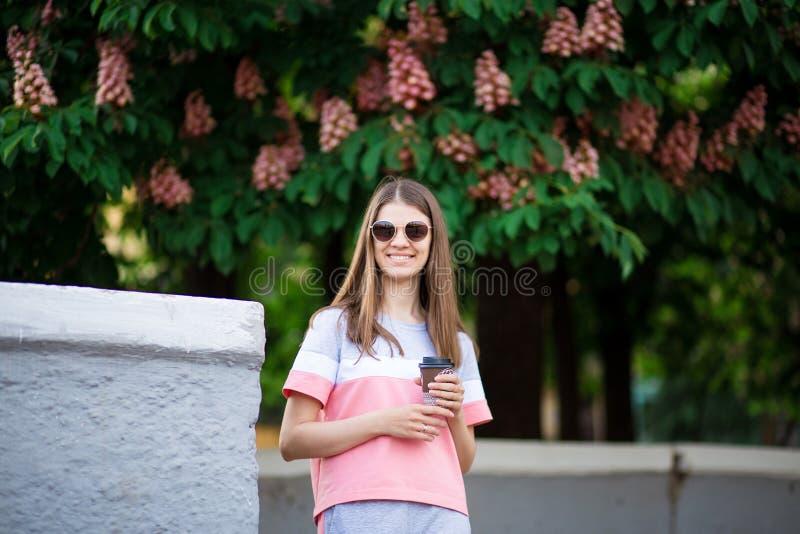 Frau, die genießende Natur des heißen Kaffees im Freien während des Feiertags am Sommertag mit Kastanie auf Hintergrund trinkt lizenzfreie stockbilder